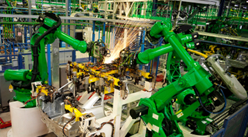 Green robotic arm in automobile factory. DKM delivers NetSuite ERP solutions for industrial equipment manufacturers.